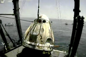In this frame grab from NASA TV, the SpaceX capsule is lifted onto a ship in the Gulf of Mexico.