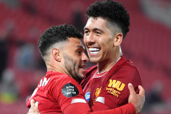 Alex Oxlade-Chamberlain of Liverpool celebrates with teammate Roberto Firmino after scoring his team's fifth goal during the Premier League match between Liverpool FC and Chelsea FC at Anfield.