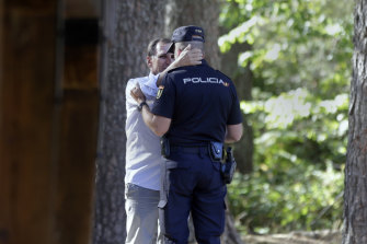 Adrian Federighi, brother in-law of Blanca Fernandez Ochoa, embraces a police officer after the search ended.