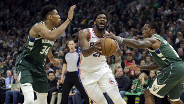 The 76ers' Joel Embiid drives between Bucks duo Giannis Antetokounmpo and Eric Bledsoe.