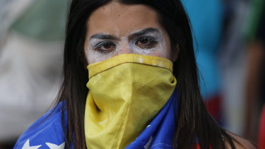 An anti-government protester wears a Venezuelan flag to cover her face, after a rally demanding the resignation of President Nicolas Maduro in Caracas last week.