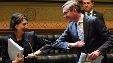 NSW Premier Gladys Berejiklian bumps elbows with Treasurer Dominic Perrottet as she congratulates him after delivering the state budget on Tuesday.