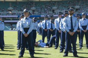 An officer collapses during the  NSW Police Force classes of 2020 Attestation Parade at Sydney Cricket Ground. 4th December 2020.