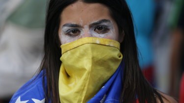 An anti-government protester covers her face with a Venezuelan flag.