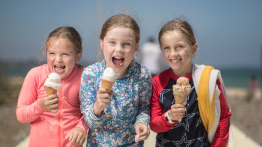 Seven-year-old friends Sofia, Eliza and Saffron share an ice-cream at Elwood beach.