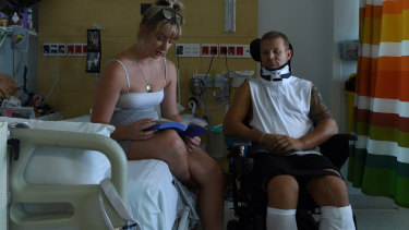 Maddi Magennis reads to her fiance Ashley Treseder at Sydney's Royal North Shore Hospital.