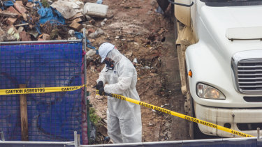 A worker in a hazardous materials suit on the Corkman Irish Pub site clears it of rubble.