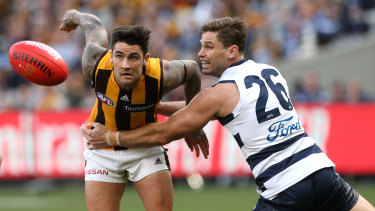 Grab and go: Hawthorn's Chad Wingard  attempts to break a tackle by Geelong forward Tom Hawkins.