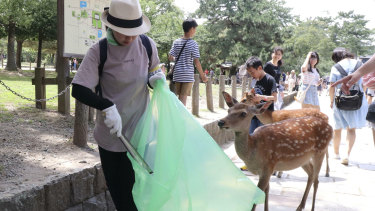 A volunteer picks up plastic rubbish during a clean-up campaign at Nara Park in western Japan on Wednesday.