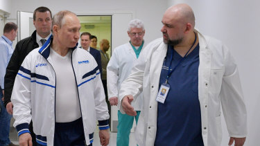 Russian President Vladimir Putin and the Kommunarka hospital's chief Denis Protsenko, right, walk in to the hospital for coronavirus patients on March 23.