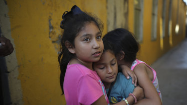 A Honduran girl, centre, is hugged by friends as she leaves a shelter after her family decided to accept voluntary return to Honduras, after spending nearly six months at the border, in Tijuana, Mexico, hoping to get to the US.