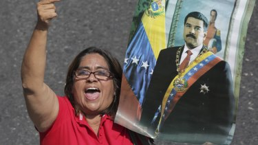 A supporter of Venezuelan President Nicolas Maduro holds a poster of him during a rally in Caracas on Labour Day.