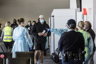 Passengers on a Jetstar flight from Melbourne are screened by NSW Health as they exit the aircraft at Sydney Airport.