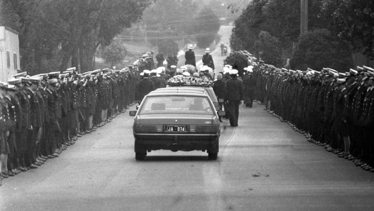 A police guard lines View Mount Road as the cortege leaves for Springvale cemetery.
