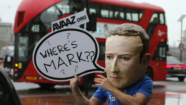 An activist wearing a Facebook CEO Mark Zuckerberg mask stands outside the meeting in Westminster.