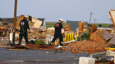 Workers look through tornado damage at the American Budget Value Inn in El Reno.