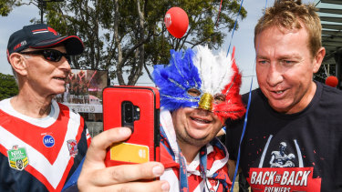 Roosters coach Trent Robinson poses for a selfie with a fan.