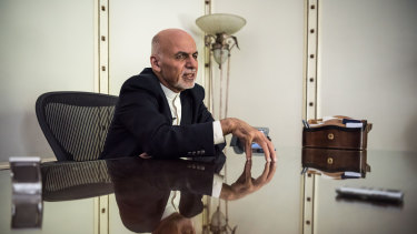 Afghan President Ashraf Ghani speaks on the phone with relatives of the Afghan soldier killed in battle, from his office in Kabul.