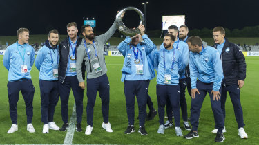 Night off: Sydney FC players show off their A-League championship trophy before the game on Tuesday night.
