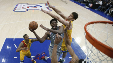 Philadelphia 76ers' Joel Embiid attempts a shot past Milwaukee Bucks' Brook Lopez and Giannis Antetokounmpo.