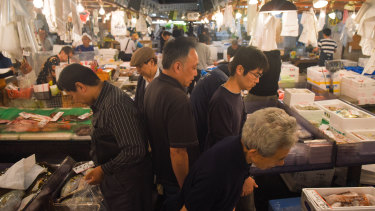 Wholesalers and customers walk through Tsukiji.  On its last day, few welcomed the prospect of an air-conditioned future.