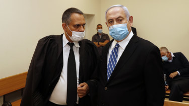 Israeli Prime Minister Benjamin Netanyahu, wearing a face mask, stands inside the court room as his corruption trial opens at the Jerusalem District Court.
