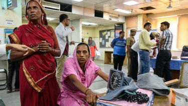 Rehmati, in pink, sits in the emergency ward of a New Delhi hospital where she arrived with symptoms of heat stroke last month.