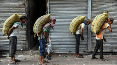 Workers carry sacks of spices on a hot summer morning in the old quarter of Delhi.