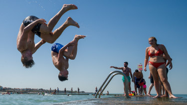 Boys somersault into the water from the lido jetty wall at Margate beach in England.