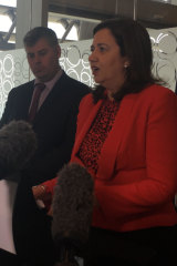Queensland Premier Annastacia Palaszczuk speaks at 1 William Street while activists chant outside.