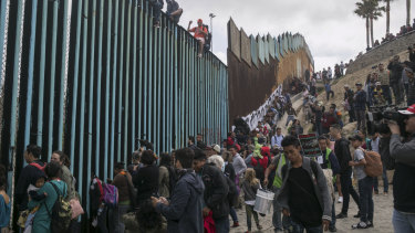 Hundreds of migrants from Central America who travelled through Mexico gather with supporters at the border wall with the US where it ends at the Pacific Ocean, in Tijuana in April.