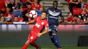 Adelaide's Mirko Boland competes with Victory's Thomas Deng.