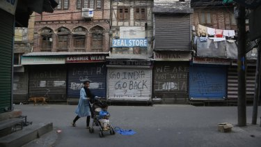 A Kashmiri woman pushes a child on a stroller past a closed market in Srinagar, Indian controlled Kashmir on Tuesday.
