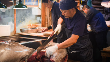 A wholesaler cuts a tuna at Tsukiji, the famed wholesale seafood market in Tokyo, on the day before its closure.