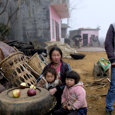 'It was a bitter experience': Xia Dayun, 33, with his wife Xu Xuanhua and their children outside the concrete house built with his earnings from migrant labour in Xinjiang.