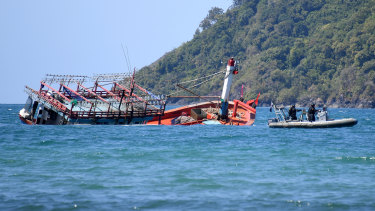 Police inspect a sunken fishing vessel, believed to be carrying Vietnamese asylum seekers, at Cape Kimberley at the mouth of the Daintree River in Queensland on Monday.