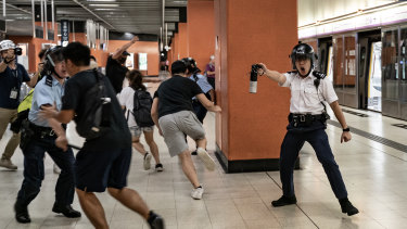 A police officer holds up pepper spray as he attempts to disperses protesters out of the platform at Po Lam Station.