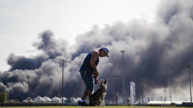 A man trains his dog with a cloud of smoke in the background from the TPC Group explosion in Port Neches, Texas.