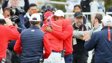 Tiger Woods embraces teammates after victory was assured.