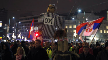 People hold a effigy representing Serbian President Aleksandar Vucic dressed as a prisoner, during a protest in Belgrade, Serbia, on Saturday.