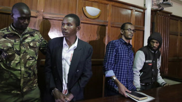 From left to right, defendants Rashid Charles Mberesero, Hassan Aden Hassan and Mohamed Abdi Abikar, are led from the dock by a police officer, left, after their verdict at a court in Nairobi, Kenya, on Wednesday.