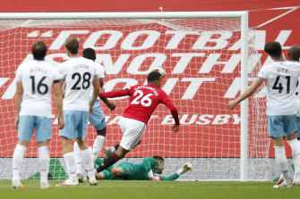 Manchester United's Mason Greenwood scores his side's opening goal during the English Premier League soccer match between Manchester United and West Ham.