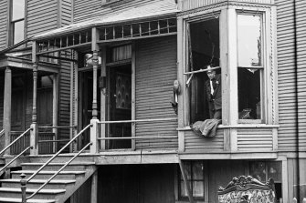 """Police look through a broken window of a house during the race riots in Chicago. Hundreds of African Americans died at the hands of white mobs during """"Red Summer"""" of 1919."""