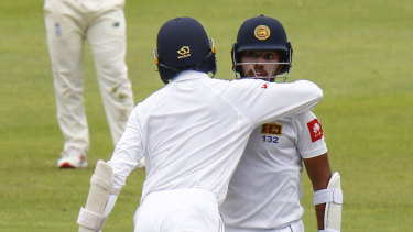 Sri Lanka's Oshada Fernando congratulates teammate Kusal Mendis on reaching his half-century.