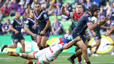 Purple reign: The Knight defence hang on to Jahrome Hughes at AAMI Park.