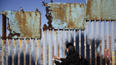 A woman takes pictures as birds sit along a rusted top section of the border wall near Tijuana, Mexico.