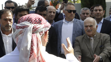 His Royal Highness Prince El Hassan bin Talal Hashemite, right, of Jordan, greets a worshipper  outside the Al Noor mosque in Christchurch, New Zealand, on Saturday.