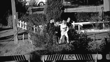 Wally and Beryl Mellish are escorted from their Glenfield home at the conclusion of the eight-day siege on July 10
