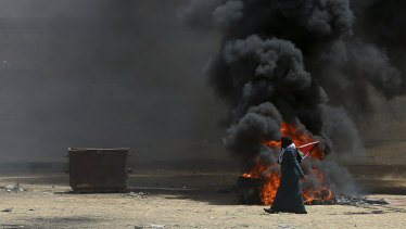 A Palestinian woman walks past burning tires near the Israeli border.