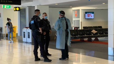 Authorised officers and Australian Federal Police at the Melbourne Airport on Saturday morning.